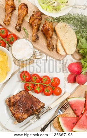 barbecue party with marinated ribs and chicken drumsticks cucumber salad with crushed pepper fresh tomato chips radish watermelon and a glass of beer