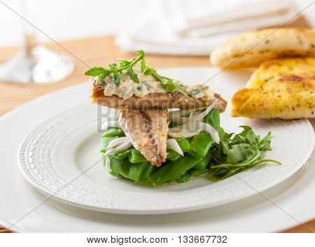 A delicious salad with green beans rocket leaves onion mackerel and tartar sauce