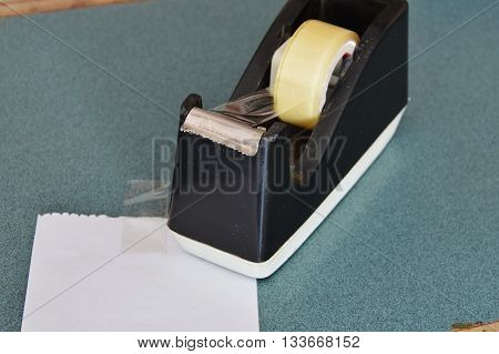 paper and black tape dispenser on counter cashier in shop