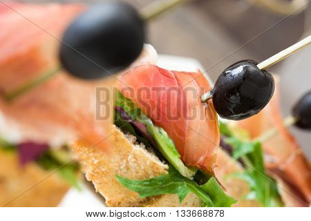 Spanish serrano ham skewer with olive and lettuce