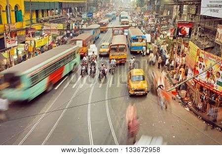KOLKATA, INDIA - JAN 17, 2016: Motion blurs from public buses cars and rushing people on indian road with many stores on January 17, 2016. Kolkata has a density of 814.80 vehicles per km road length