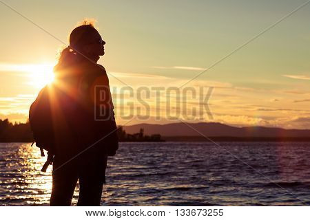 free silhouette woman standing near the lake among the mountains clouds backlit at sunset