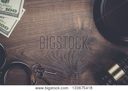 handcuffs gavel and money on the wooden background