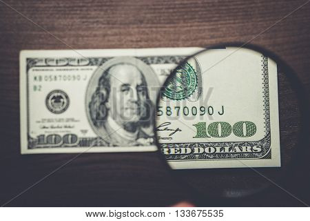 one hundred dollars banknote authentication on wooden background