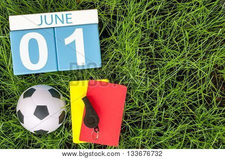 June 1st. Image of june 1 wooden color calendar on green grass background with football outfit. First summer day.