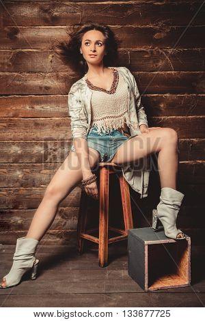 Beautiful brunette girl in short shorts posing in studio on wooden background
