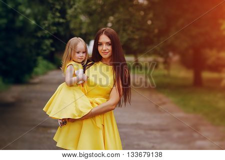 beautiful young mother with  small daughter walks through city