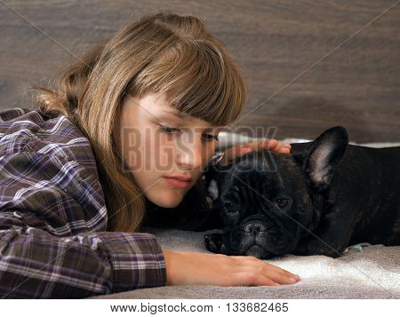Sad dog lying on the bed. Young girl petting a dog calms