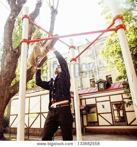 Father with son on playground training, happy real family smiling outside, lifestyle people concept, fathers day