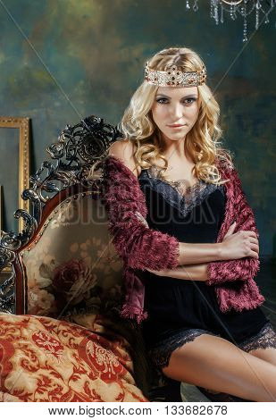 young blond woman wearing crown in fairy luxury interior with empty antique frames total wealth, magic rich concept real people