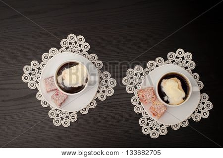 Two mugs of coffee with ice-cream Turkish delight on a saucer on white lace napkins. Top view black background