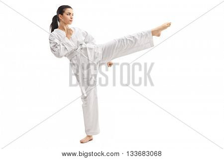 Studio shot of a young woman practicing martial arts in white kimono isolated on white background