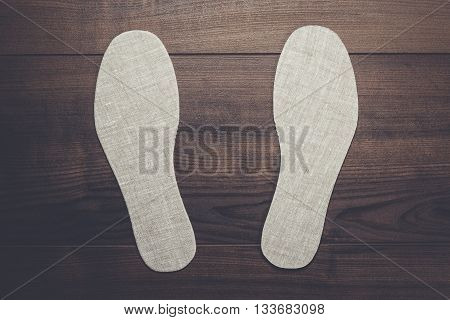 grey insoles for shoes over wooden background