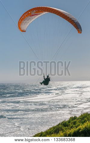 PORT ELIZABETH SOUTH AFRICA - FEBRUARY 27 2016: Silhouette of a paraglider in the air at Beachview near Port Elizabeth