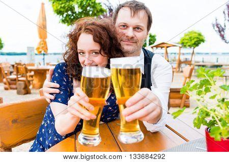 couple toasting toward friends in beer garden pub