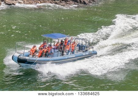 STORMS RIVER MOUTH SOUTH AFRICA - FEBRUARY 29 2016: Unidentified tourists on an inflatable speedboat on the Storms River waving for the camera