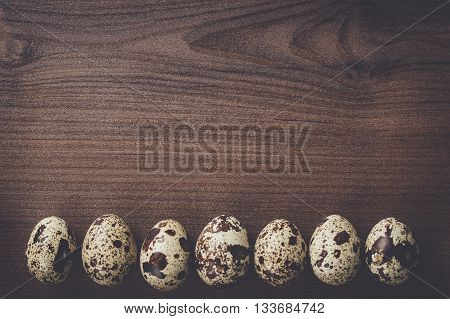 some quail eggs on the brown wooden table background