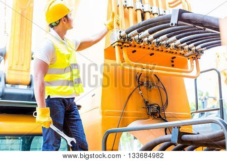 Asian motor mechanic standing in front of construction or mining machinery in vehicle workshop