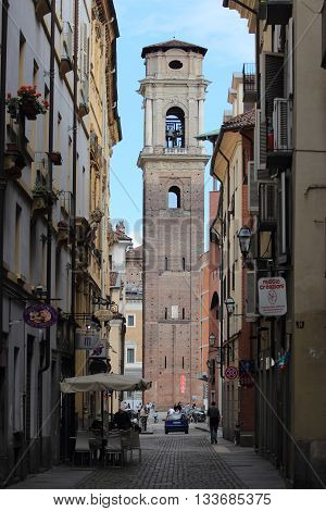TURIN ITALY - JUNE 5 2016: local life with a sight of the bell tower of Saint John the Baptist Cathedral