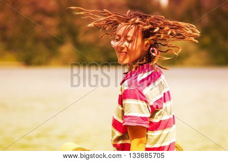 young girl with dreadlocks circling on the nature