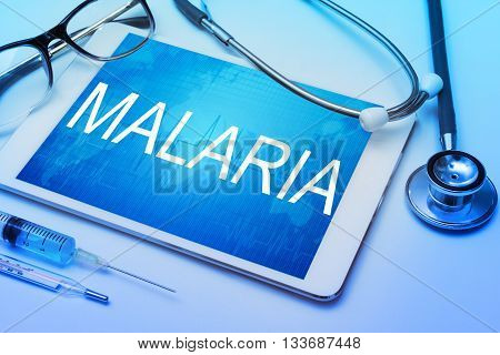 Malaria word on tablet screen with medical equipment on background.