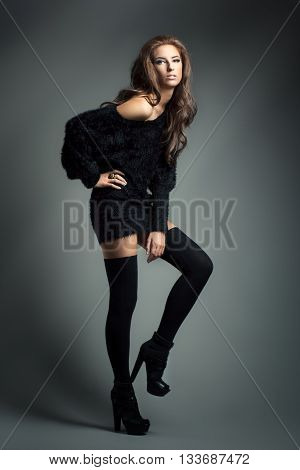Fashion portrait of young elegant woman. Black cardigan. Studio shot