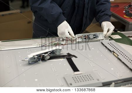 Electronic technician at work. Manual work in electronic industry.