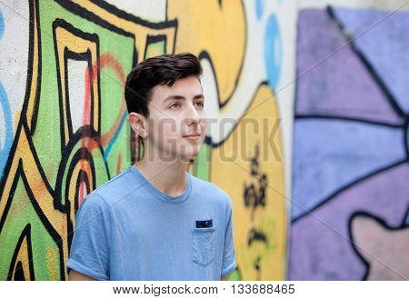 Portrait of a teenager rebellious man on a wall with graffiti background