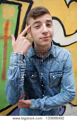 Pensive and funny teenager on a wall with graffiti background