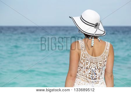 Woman standing on a beach facing away from the camera looking at marvelous breathtaking turquoise sea