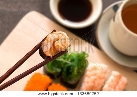 Sushi set with chop sticks wasabi served on wooden slate selective focus - Sushi is food originating in Japan consisting of cooked vinegar rice combined with other ingredients such as vegetables