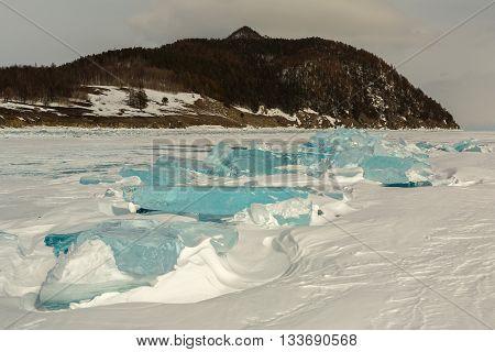 Transparent ice near the Holy Nose Peninsula. Beautiful winter landscape in the Lake Baikal.