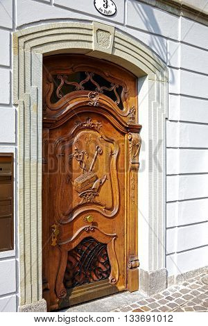 LUCERNE SWITZERLAND - MAY 02 2016: Carved with irregular pattern wooden entrance door to the old building located in the old town. Handle on the door is positioned exceptionally low to the ground