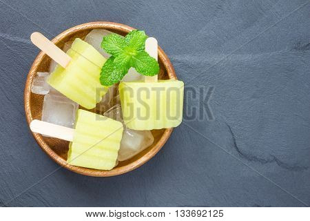 Homemade melon popsicles on grey slate top view
