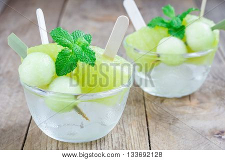 Homemade melon popsicles in the glass on a wooden table