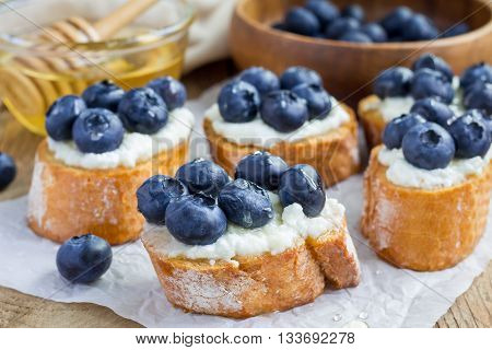 Crostini with ricotta cheese blueberries and honey on parchment paper