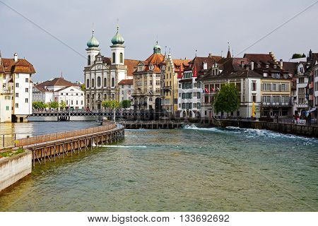 LUCERNE SWITZERLAND - MAY 02 2016: View towards the Jesuit Church and other colorful townhouses by the river Reuss in old town shows unique character of the City and multitude of tourist attractions