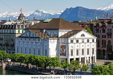 LUCERNE SWITZERLAND - MAY 06 2016: White Theater building is located along the river and surrounded by other buildings. Alpine Landscape highlights the unique character of the city