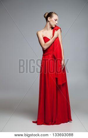 Portrait of elegant blonde model in long dress holding red cloth on shoulder.Studio shot