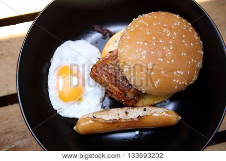 Burger with chicken and egg on black dish, Wooden Background,Fast Food and Junk food