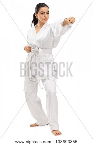 Full length portrait of a young female martial artist punching isolated on white background