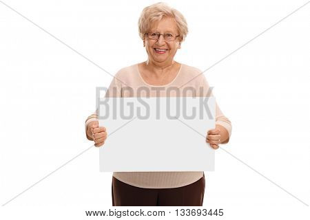 Senior lady holding a blank white signboard and looking at the camera isolated on white background