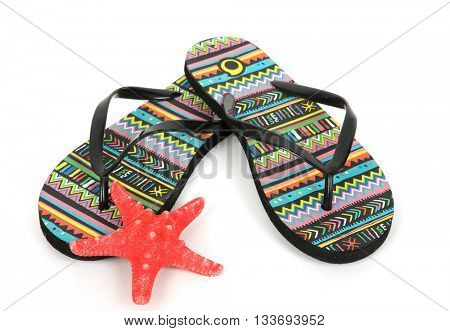 Colorful striped flip flops and seashell