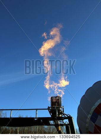 Orange flame bursts from the gas burners of the balloon on blue sky background Dmitrov Russia