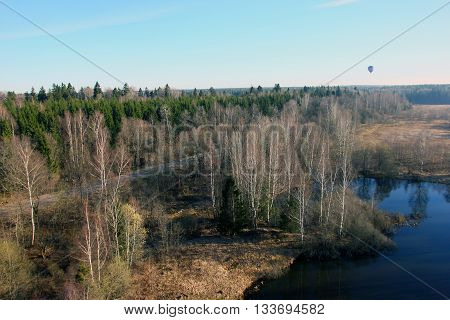 views of field fir forest lake clear sky and balloon from the birds eye view from a hot air balloon at the morning