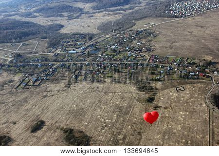 red balloon in the shape of red heart hovers over the terrain - fields village and forests in morning - birds eye view