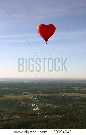 red balloon in the shape of red heart hovers over the terrain - fields meadows and forests in morning with clear blue sky