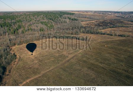 views of field and forest from the birds eye view from a hot air balloon and shadow of balloon on the field