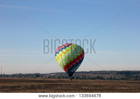 Beautiful multi-colored balloon lands in a field at the morning Dmitrov Russia