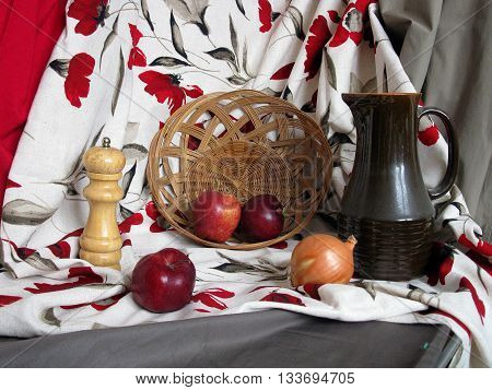 staged still life with red grey and white color drapery apples onion basket and jar